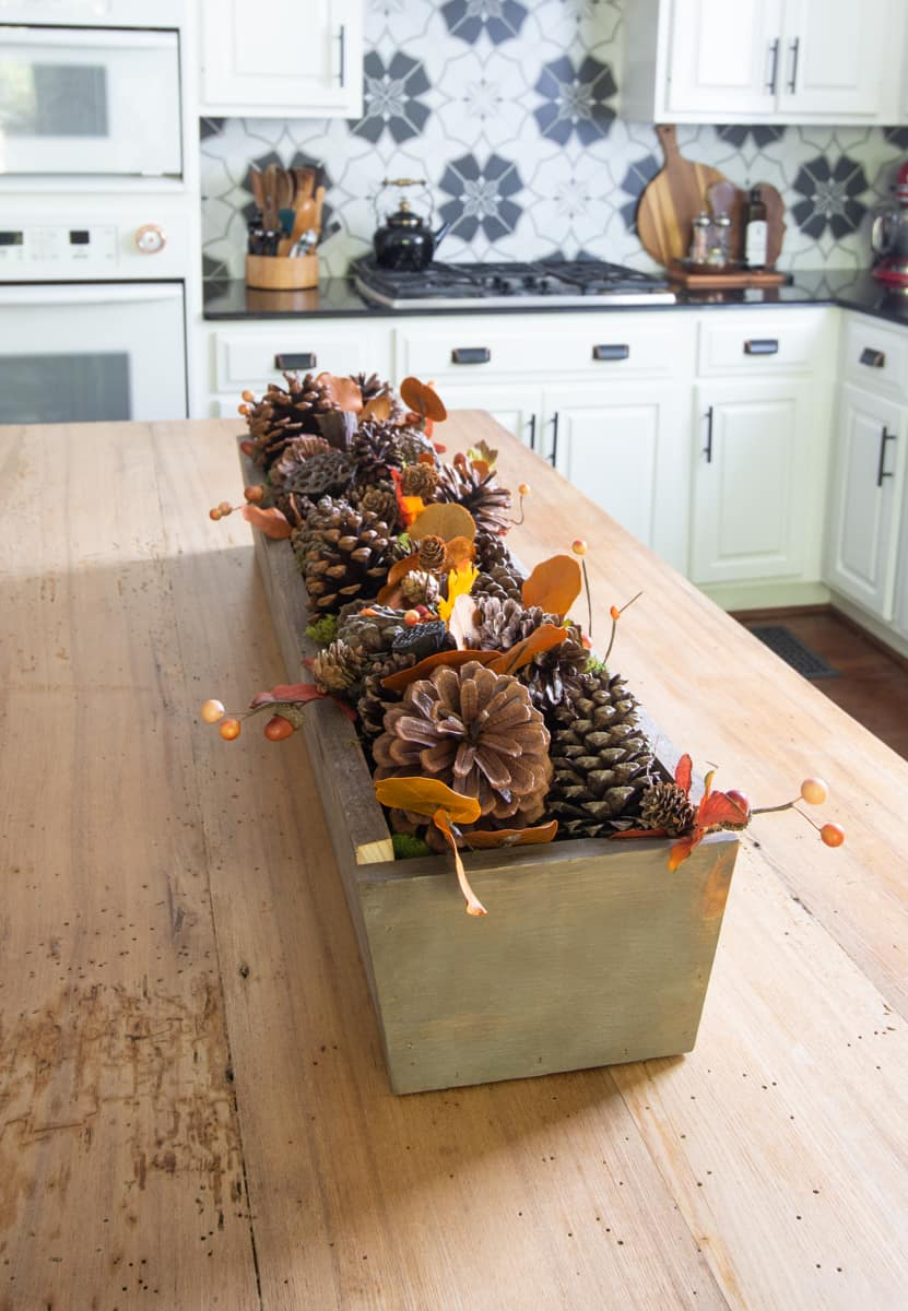 Fall centerpiece with pine cones and leaves